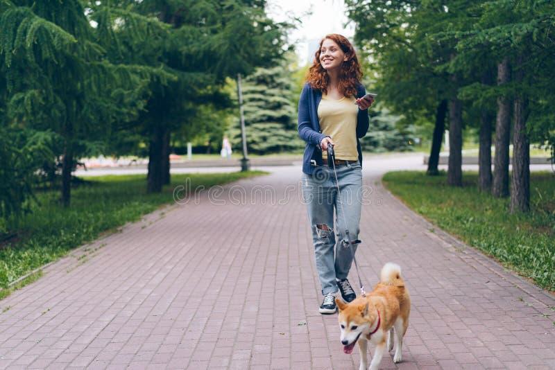 Śliczny dziewczyny odprowadzenie z psem w zieleń parku trzyma mądrze telefonu ono uśmiecha się obrazy stock