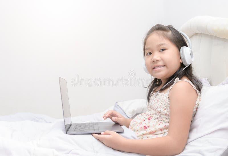 Śliczny dziewczyny sztuki laptop i słuchająca muzyka zdjęcia royalty free