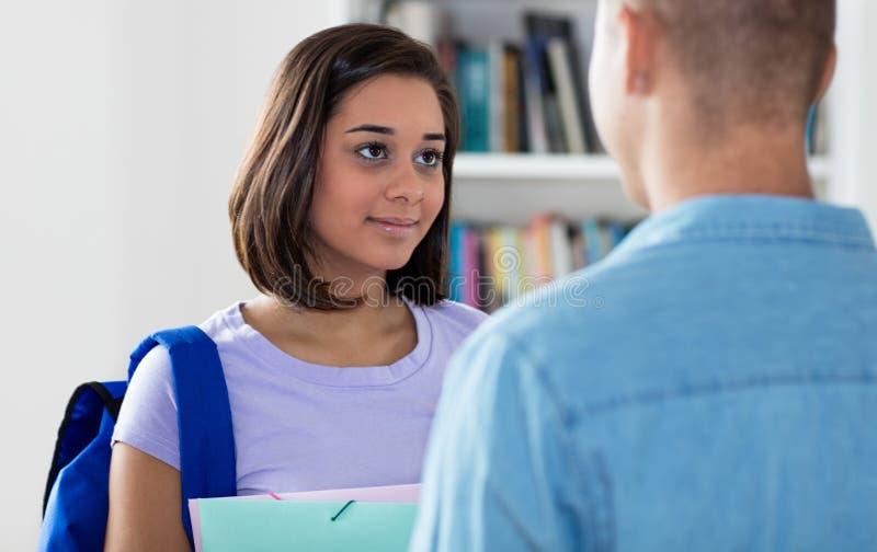 Śliczny hiszpański żeński uczeń opowiada z przyjacielem zdjęcie stock