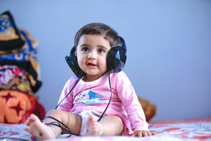 Śliczny indianin, azjatykcia mała dziewczyna słucha muzyka na hełmofonach/ zdjęcia royalty free