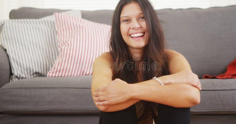 Śliczny kobiety obsiadanie w żywy izbowy roześmianym uśmiechnięty i obraz stock