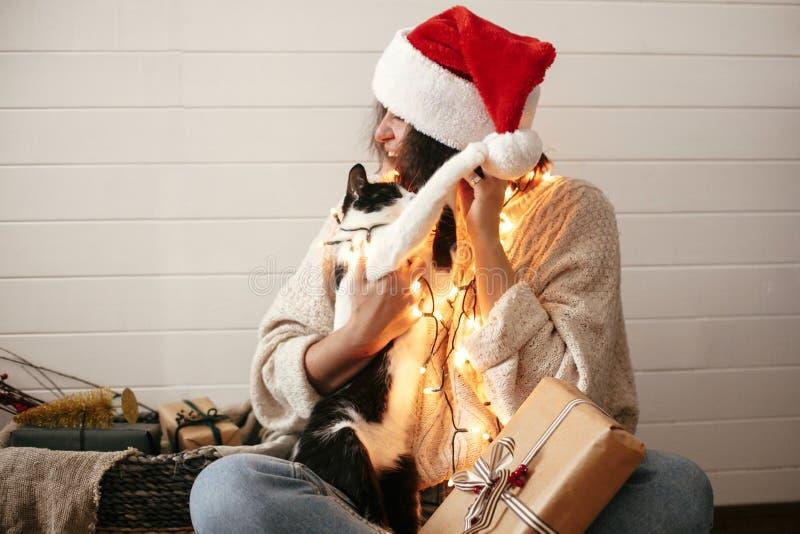 Śliczny kot bawić się z Santa kapeluszem na eleganckiej szczęśliwej dziewczynie w świątecznych bożonarodzeniowych światłach na tl obraz stock