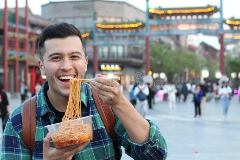 Śliczny mężczyzna je szybkiego posiłek outdoors zdjęcie royalty free