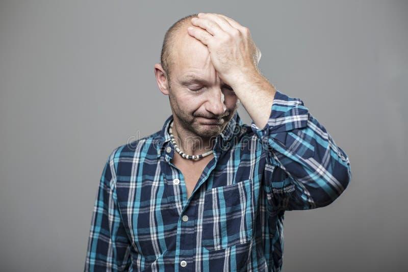 Śliczny mężczyzna migrenę i zamykał jego oczy, stawia jego rękę jego czoło, odizolowywających na szarym tle zdjęcia royalty free