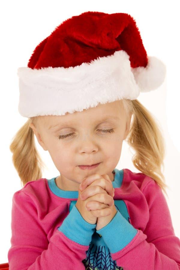 Śliczny młodej dziewczyny modlenie jest ubranym Santa kapelusz obraz stock