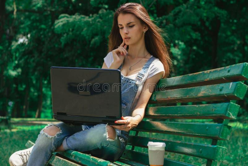 Śliczny młodej dziewczyny obsiadanie na ławce w parku z czarnym laptopem zdjęcie stock