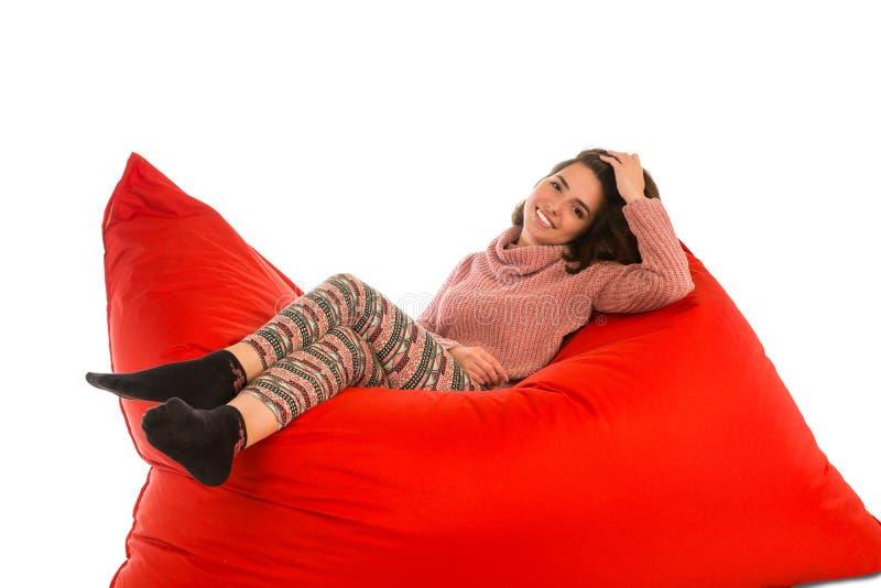 Śliczny młodej kobiety lying on the beach na plac czerwony kształtującym beanbag kanapy krześle ja fotografia stock