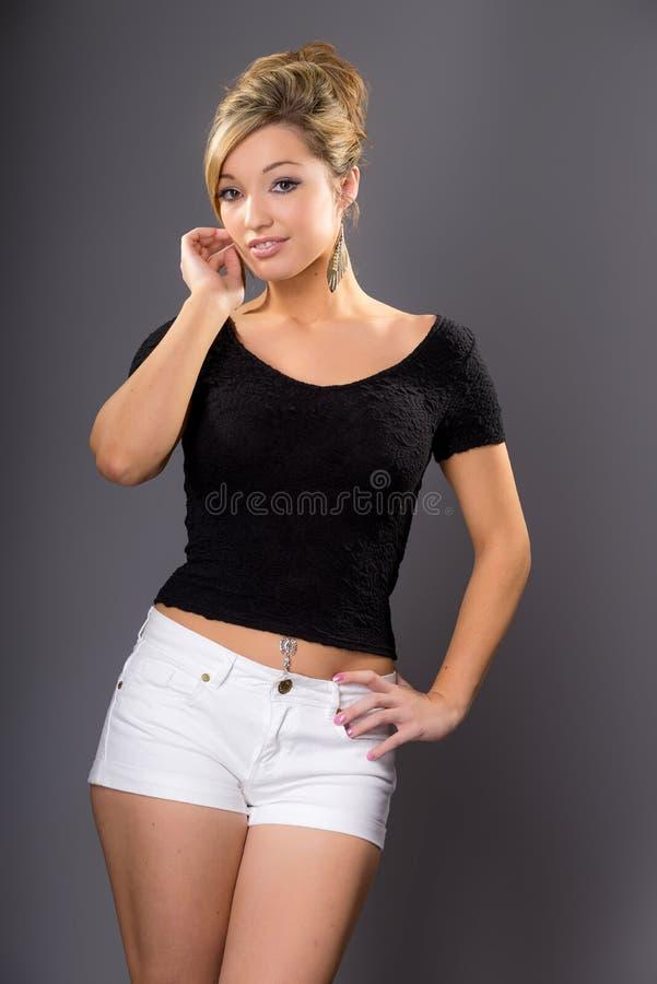 Śliczny młody blondynka model, pozujący w białym zmroku wierzchołku i skrótach zdjęcia stock
