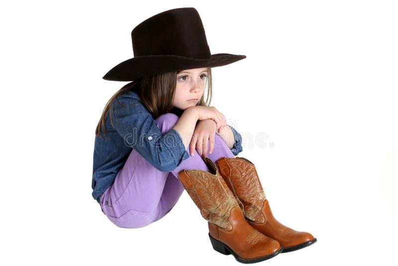 Śliczny młody cowgirl obsiadanie z jej kolanami up fotografia stock