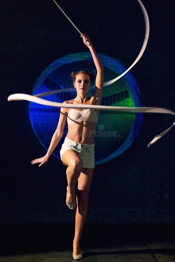 Śliczny młody gimnastyczki kobiety szkolenie z gimnastyki taśmą na ciemnym tle fotografia royalty free