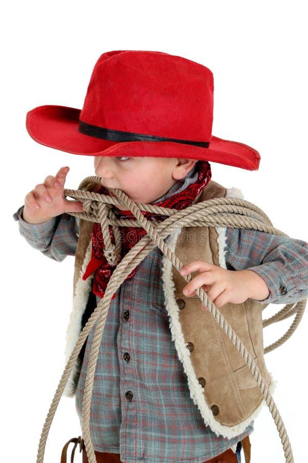 Śliczny młody kowbojski berbeć gryźć linowego jest ubranym czerwonego kapelusz obrazy stock
