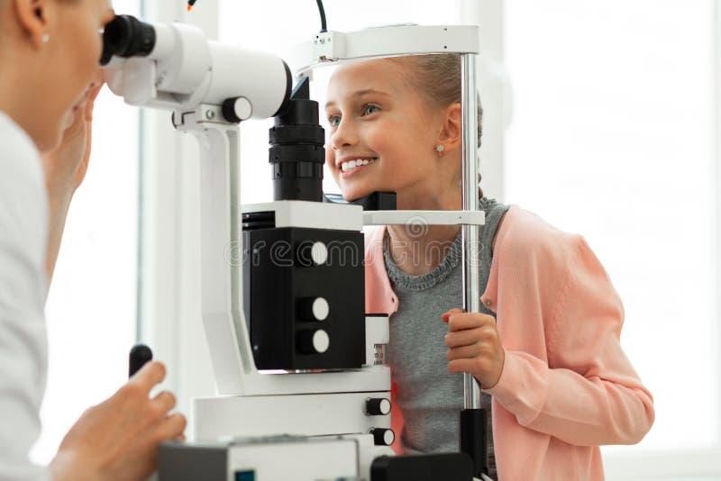 Śliczny młody pacjent spokojnie znosi procedurę z niebieskimi oczami obrazy stock