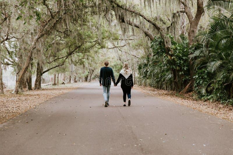 Śliczny Młody Szczęśliwy Kochający pary odprowadzenia puszek Stara Zaniechana droga z Mechaty Dębowych drzew Nadwiesić obrazy royalty free