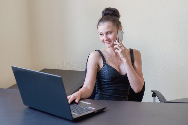 Śliczny młody urzędnik opowiada na telefonie komórkowym w biurze zdjęcie royalty free