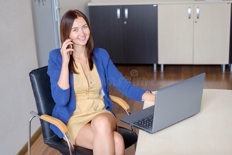 Śliczny młody urzędnik opowiada na telefonie komórkowym w biurze obrazy stock