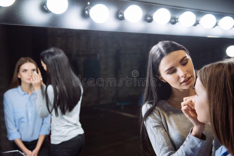 Śliczny młody visagiste stosuje makeup obraz stock