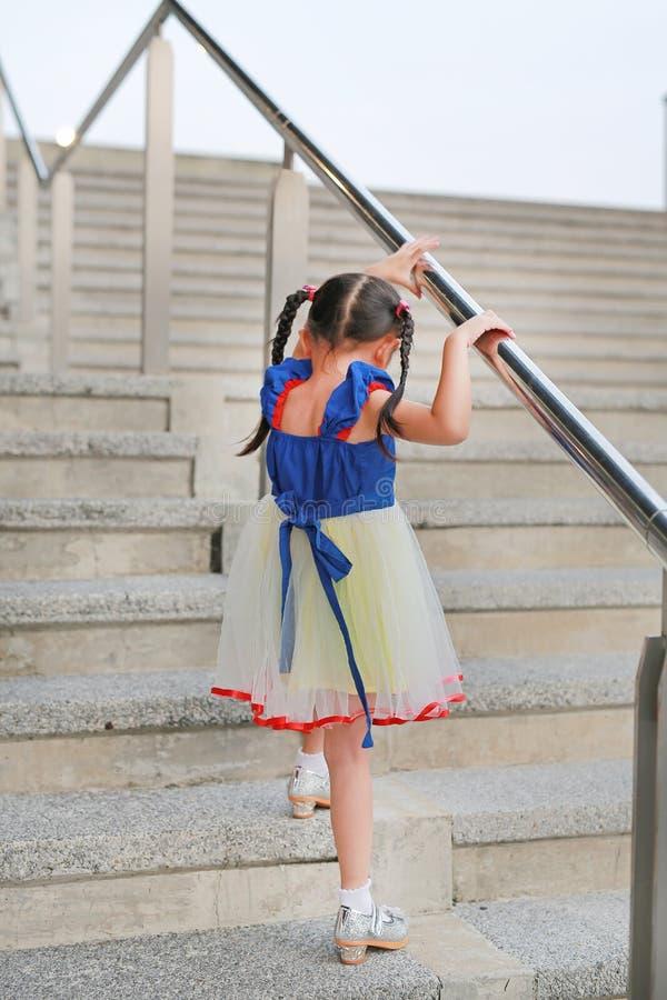 Śliczny małe dziecko dziewczyny odprowadzenie na w górę schodowego poręcza odosobniony tylni widok biel obrazy royalty free