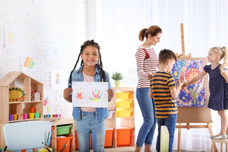 Śliczny małe dziecko pokazuje prześcieradło papier z kolorowymi ręka drukami indoors obraz royalty free