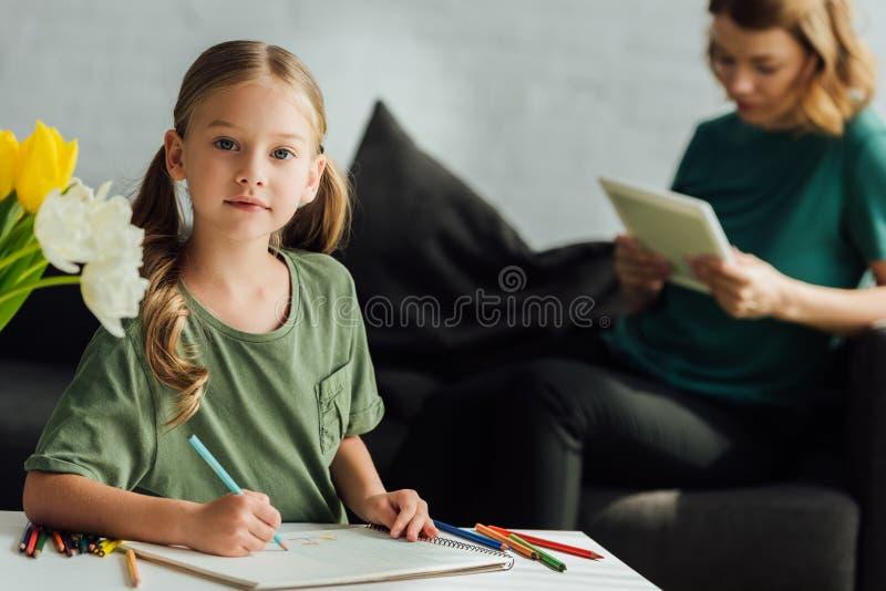 śliczny małe dziecko rysunek z barwionymi ołówkami i patrzeć kamerę podczas gdy macierzysty używać cyfrowy zdjęcie stock