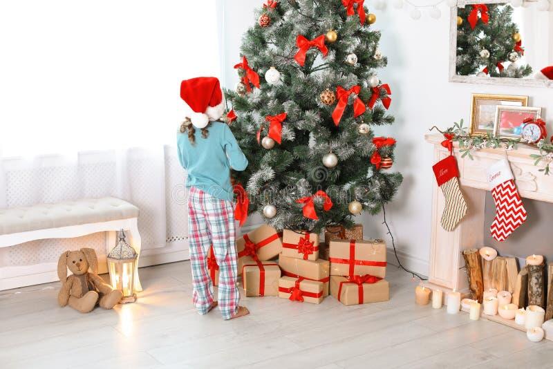 Śliczny małe dziecko w Santa kapeluszowej pobliskiej choince zdjęcie stock