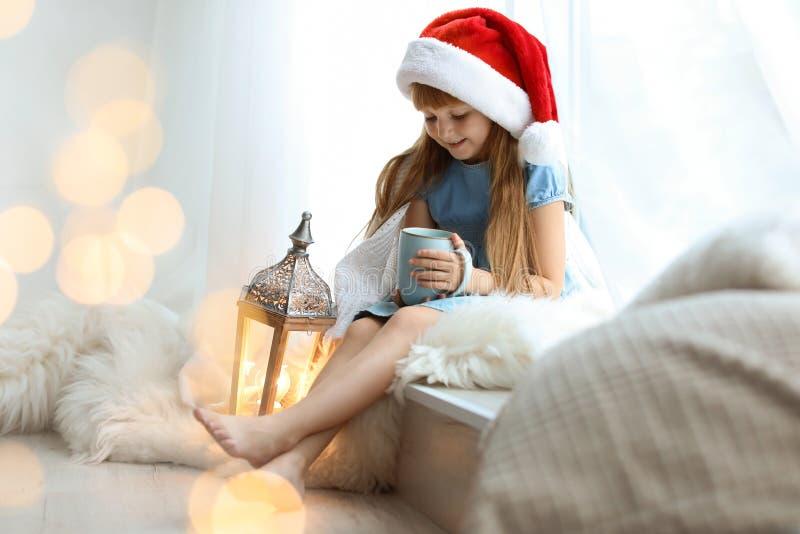 Śliczny małe dziecko w Santa kapeluszu z filiżanką kakaowy obsiadanie zdjęcia stock