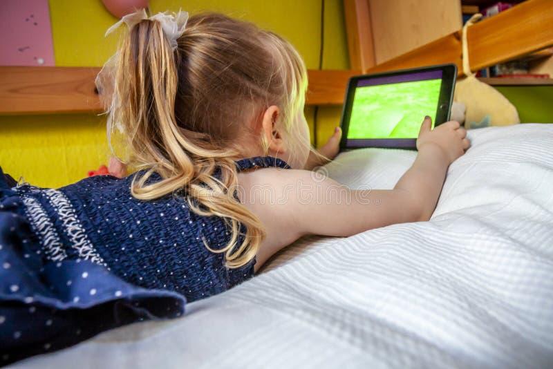 Śliczny małej dziewczynki lying on the beach na łóżku i używać jej pastylka komputer zdjęcie royalty free