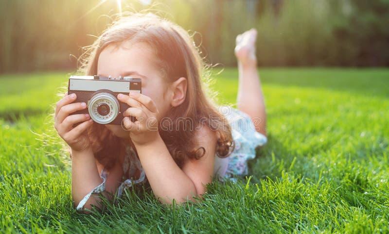 Śliczny małej dziewczynki lying on the beach na zielonym gazonie i brać obrazek zdjęcie royalty free