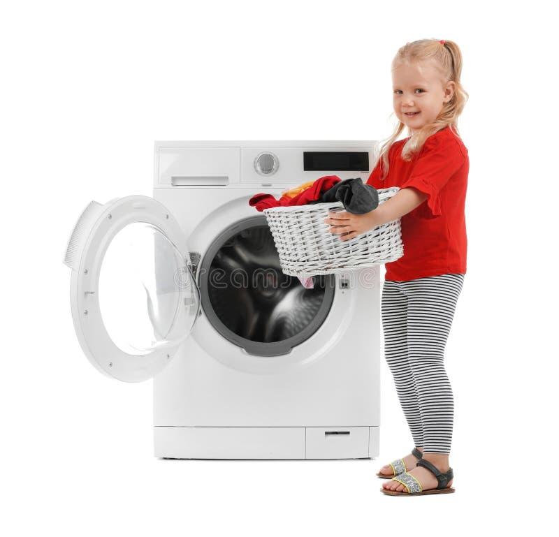 Śliczny małej dziewczynki mienia kosz z pralnianą pobliską pralką fotografia royalty free