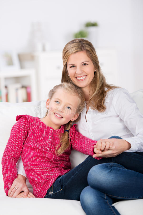 Śliczny małej dziewczynki obsiadanie na kanapie z jej matką zdjęcie royalty free