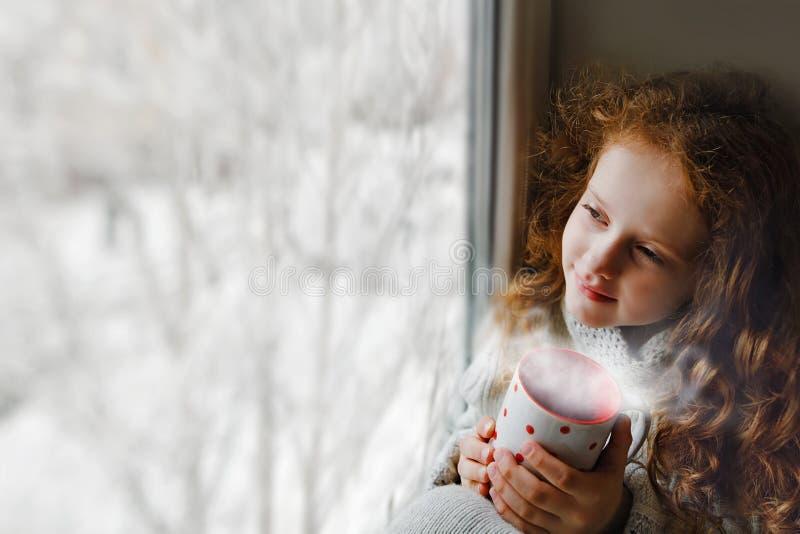 Śliczny małej dziewczynki obsiadanie z filiżanką gorący coffe okno fotografia royalty free