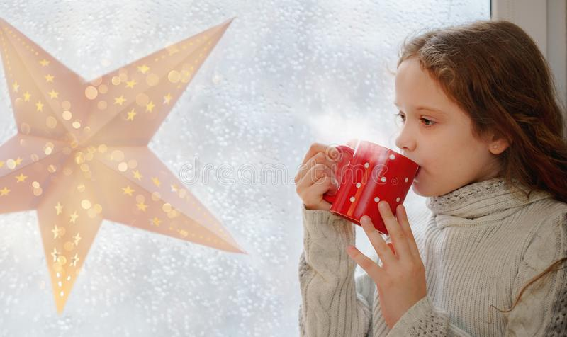 Śliczny małej dziewczynki obsiadanie z filiżanką gorący kakao okno zdjęcia stock