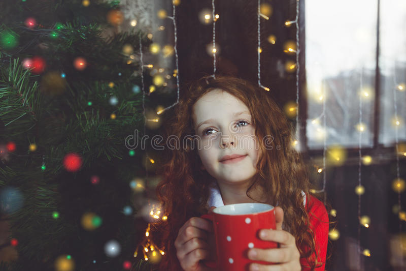 Śliczny małej dziewczynki obsiadanie z filiżanką gorący kakao okno obraz stock
