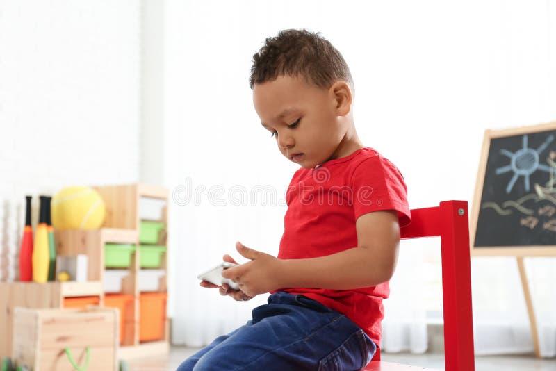 Śliczny mały afroamerykański dziecko bawić się na telefonie komórkowym w dziecinu, przestrzeń dla teksta zdjęcia stock