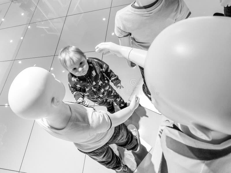 Śliczny mały blondynki dziewczyny mienie wręcza białych mannequins i spojrzenia w ich twarze obrazy royalty free