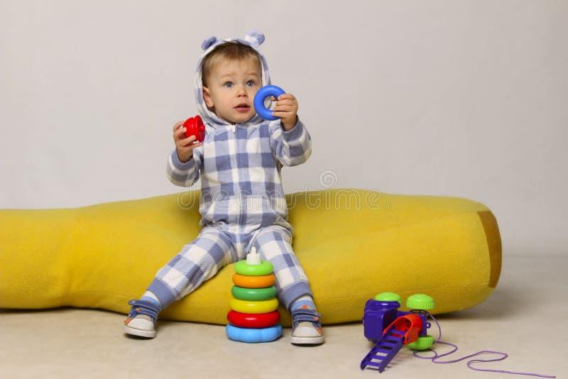 Śliczny Mały chłopiec obsiadanie Na Żółtym Bobowej torby krześle i Bawić się zabawkach obraz stock