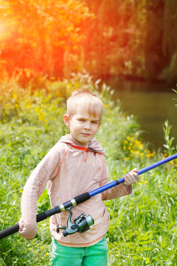 Śliczny mały chłopiec stojak blisko rzeki z połowu prąciem w jego ręki obrazy royalty free