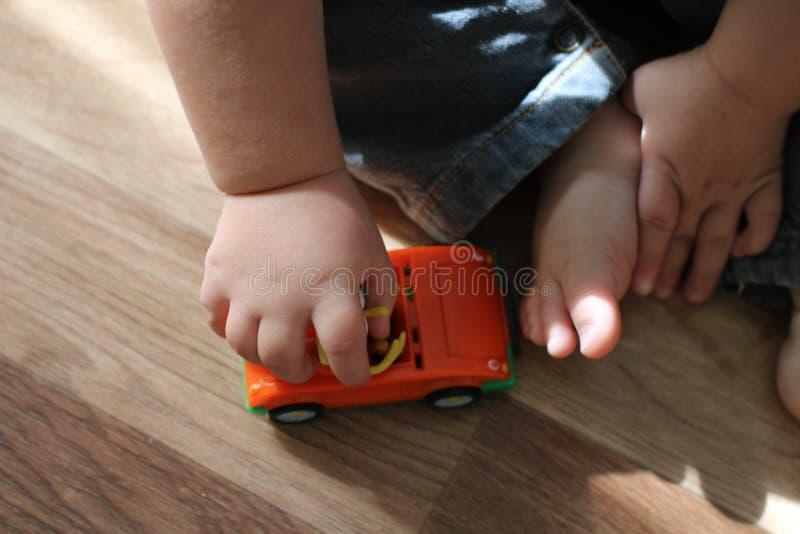 Śliczny mały dziecko bawić się z zabawkarskim samochodowym obsiadaniem na drewnianej podłoga Zakończenie w górę dziecko ręk trzym obrazy stock