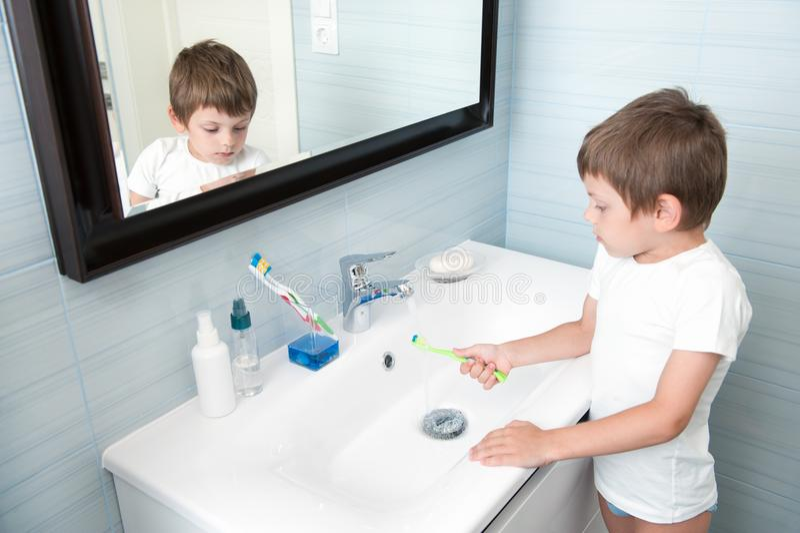 Śliczny mały dziecko myje jego toothbrush pod strumieniem woda w łazience zdjęcie royalty free