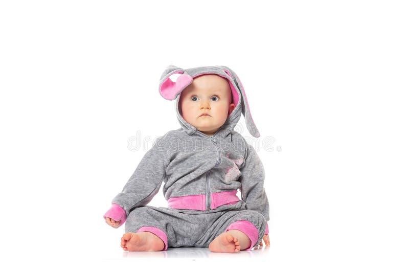 Śliczny mały dziecko w królika kostiumowym obsiadaniu na białym tle dziecka ` s gry ręce 14 dni ojciec dziecka emocje jego dziewc zdjęcie stock