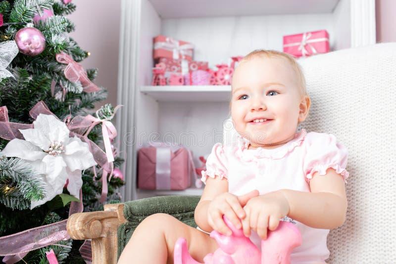 Śliczny mały dziecko w rocznika krześle i boże narodzenie prezentach Małe dziecko ma zabawę blisko choinki w żywym pokoju fotografia stock