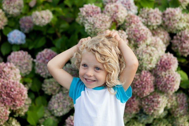 Śliczny mały dziecko z dużo kwitnie w ogródzie zdjęcia royalty free