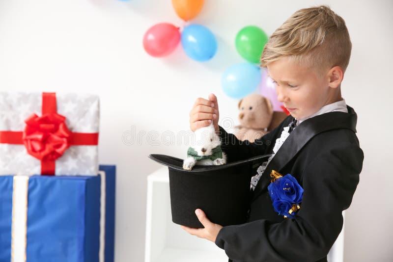 Śliczny mały magika ciągnięcia królik z kapeluszu indoors zdjęcia stock