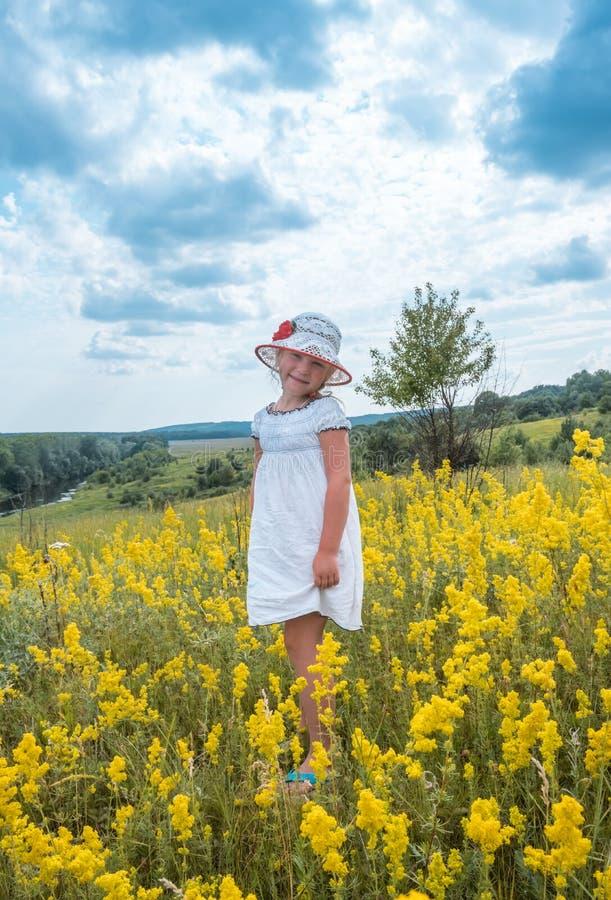 Śliczny mały roześmiany dziewczyny odprowadzenie w polu żółci kwiaty zdjęcia stock