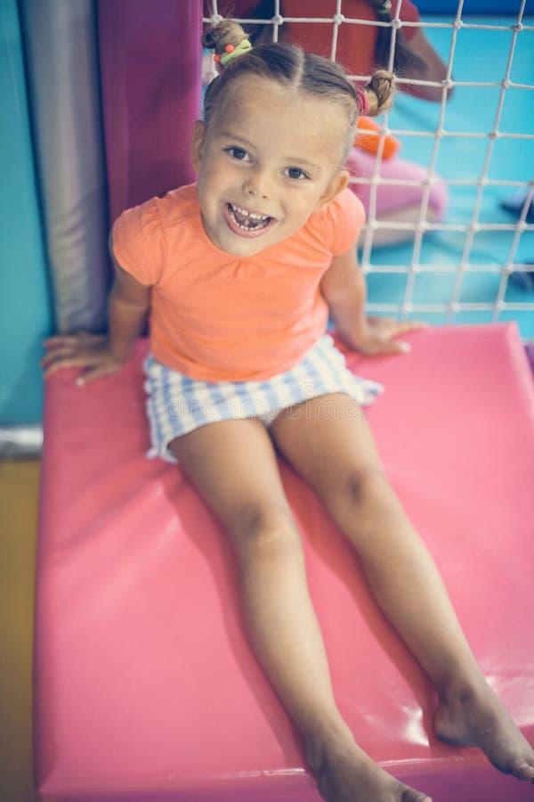 Śliczny mały uśmiechnięty dziewczyny obsiadanie na macie Małej dziewczynki kursowanie w p obraz royalty free