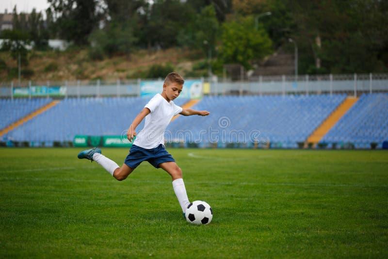 Śliczny nastoletni chłopak uderza futbolową piłkę na stadium tle Dzieci Trenuje piłkę nożną Sporta pojęcie obrazy royalty free