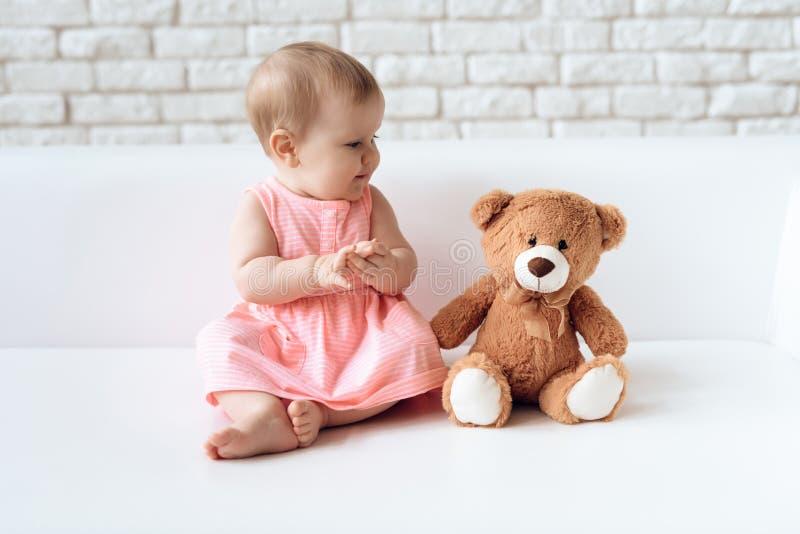 Śliczny nowonarodzony dziecko na kanapie z mokietu niedźwiedziem zdjęcia stock