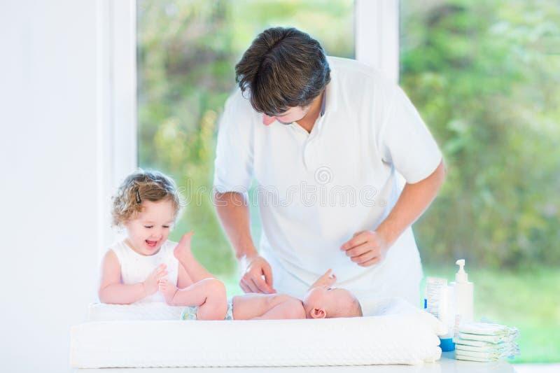 Śliczny nowonarodzony dziecko patrzeje ojca i berbecia siostry fotografia royalty free