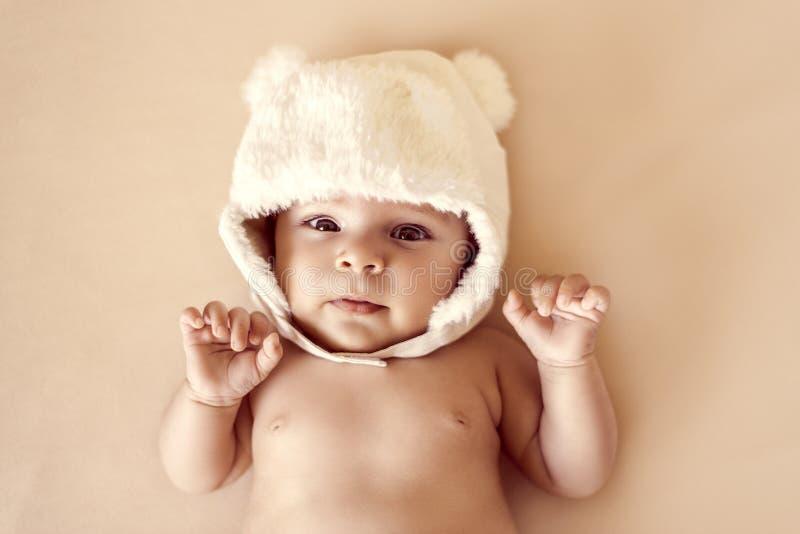 Śliczny nowonarodzony dziecko w zima ciepłym kapeluszu z niedźwiadkowych ucho śmiesznym lying on the beach obrazy royalty free