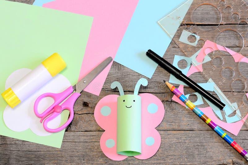 Śliczny papierowy motyl, nożyce, markier, kleidło kij, barwił papieru set i świstki, władca, ołówek na starym drewnianym stole Dz zdjęcia stock