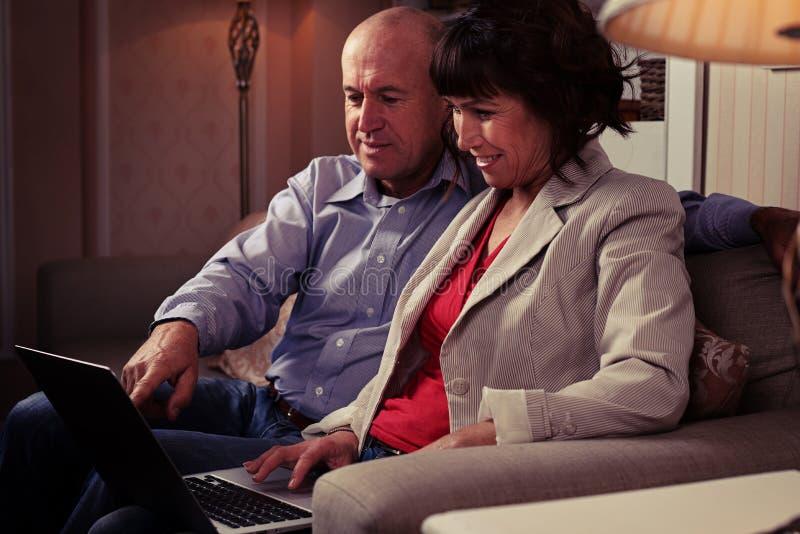 Śliczny pary dopatrywanie coś na notatniku indoors fotografia royalty free